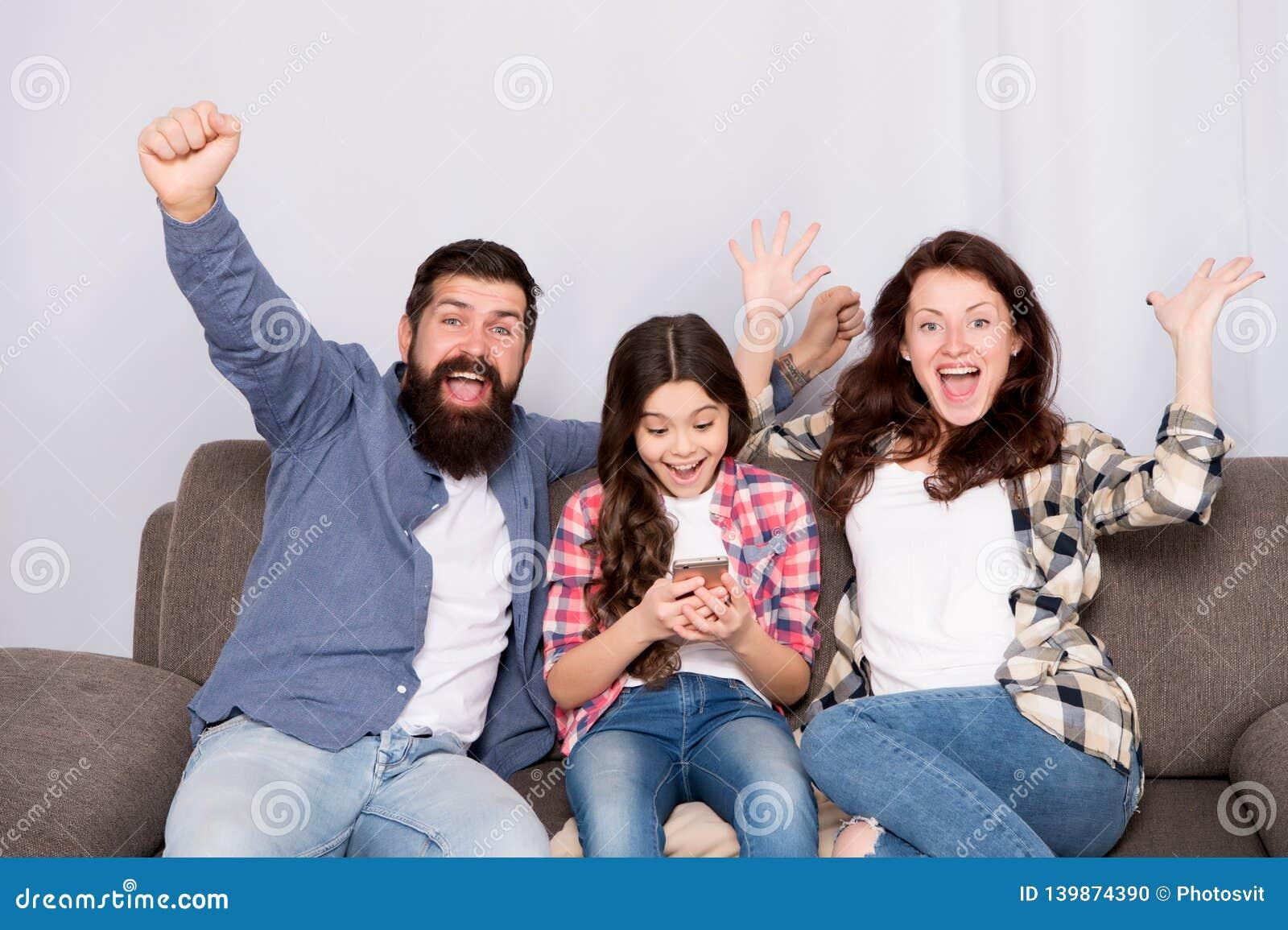 Смартфон пользы маленькой девочки ребенка с родителями Дружелюбная семья имея потеху совместно Папа мамы и занятая дочь ослабляя