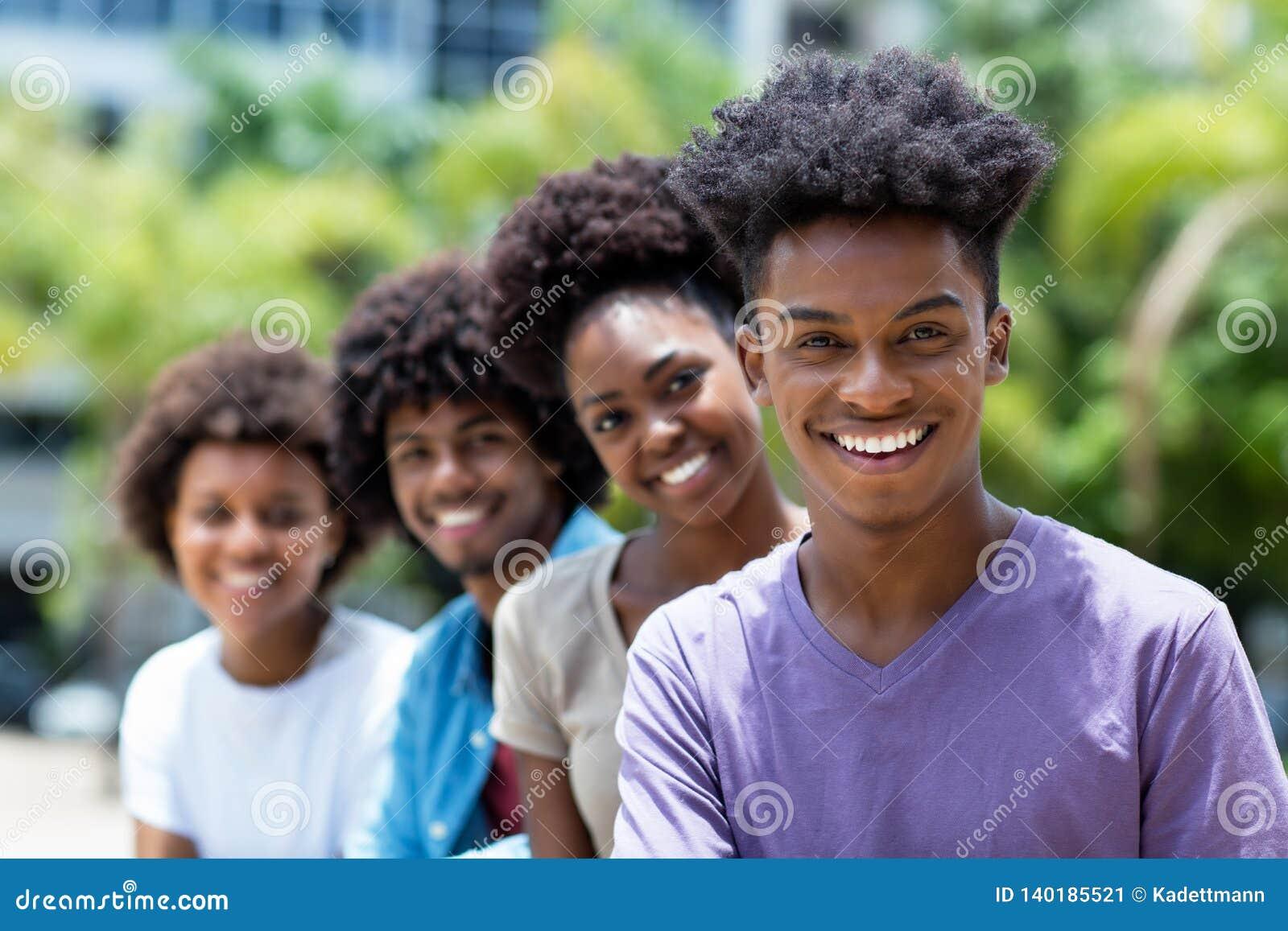 Смеясь Афро-американский человек с группой в составе молодые взрослые в линии