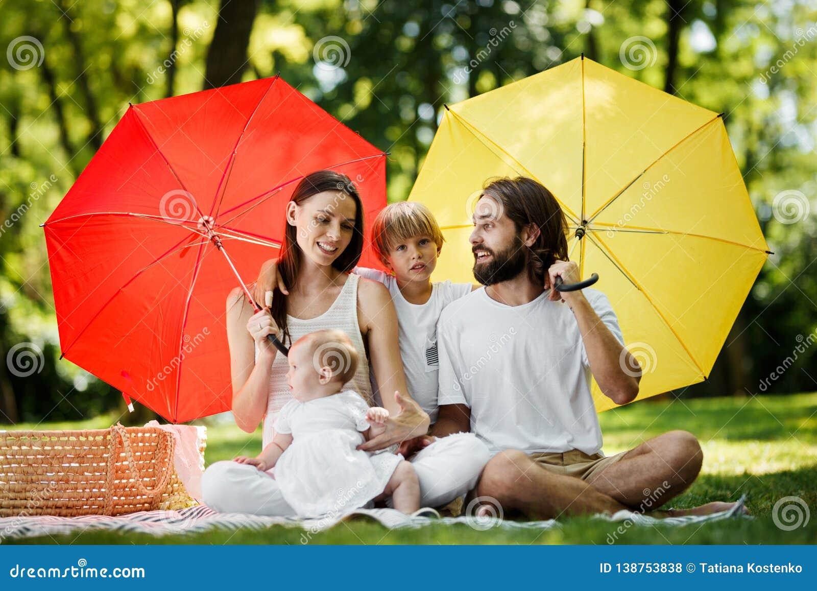 Смешные дети с мамой и папой сидя на одеяле под большими красными и желтыми зонтиками покрывая их от солнца