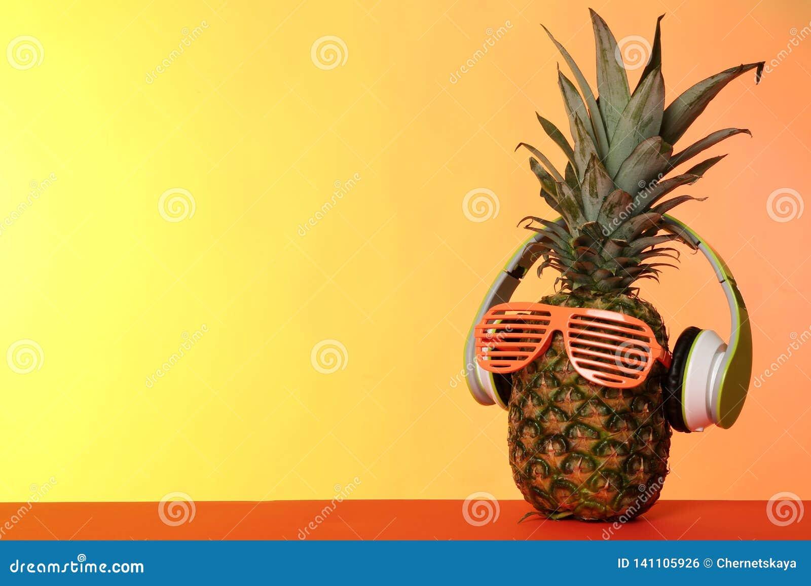 Смешной ананас с наушниками и стеклами партии на предпосылке цвета