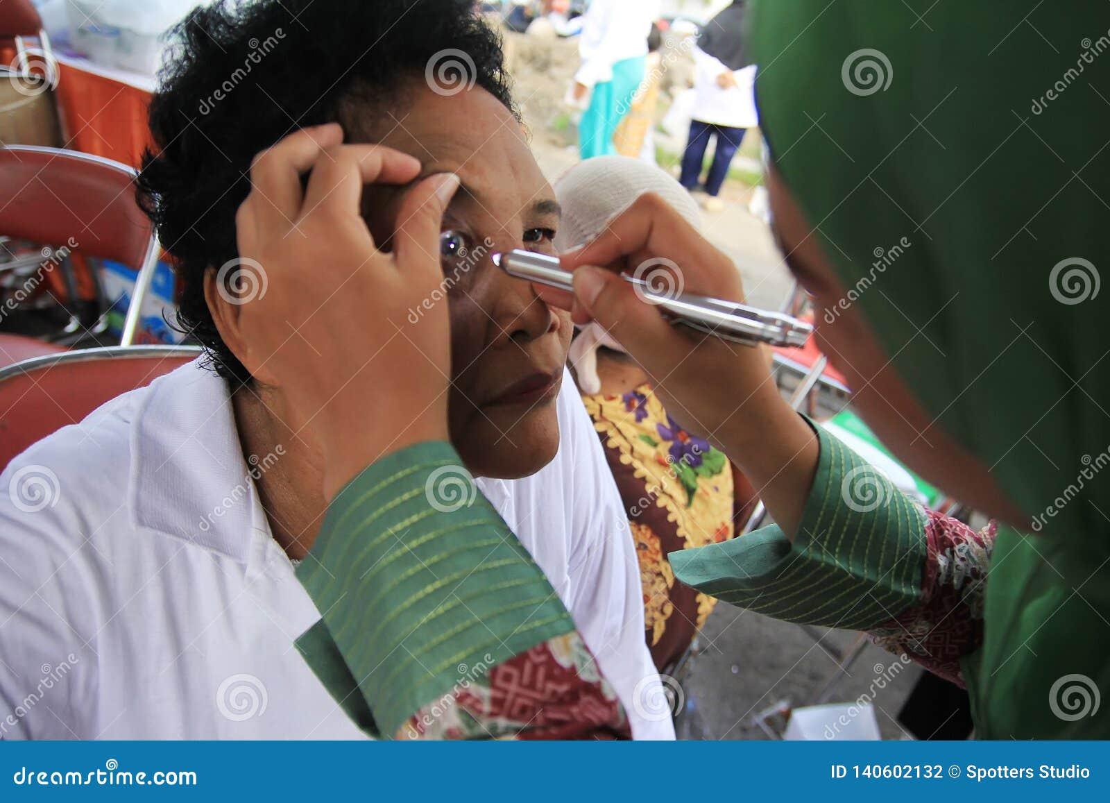 Сурабая Индонезия, может 21, 2014 работник службы здравоохранения проверяет глаза пациента