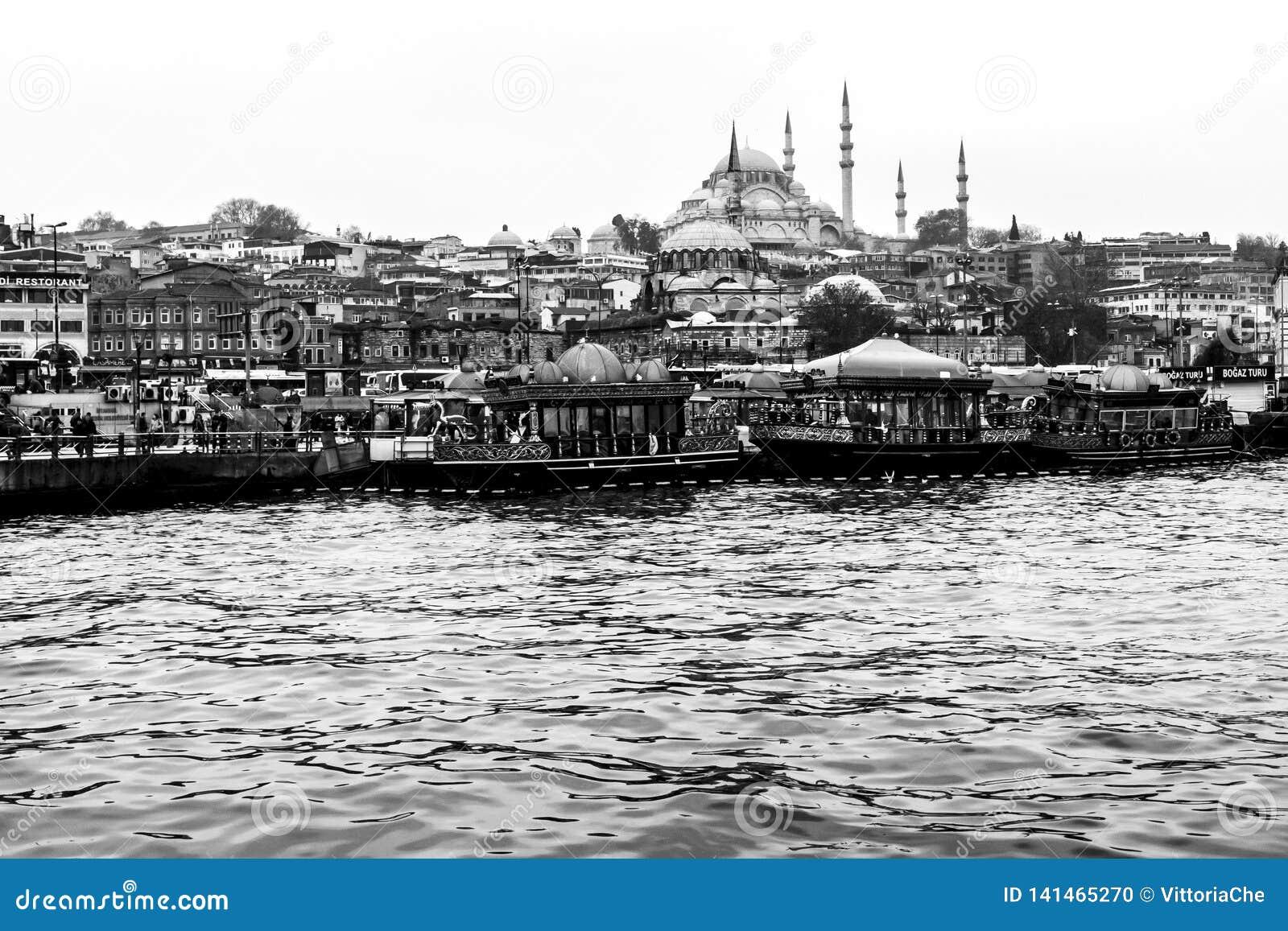 Стамбул, Турция - 6-ое декабря 2014: Взгляд мечети Suleymaniye от золотого рожка, людей посещает кафе в шлюпках и дозоре