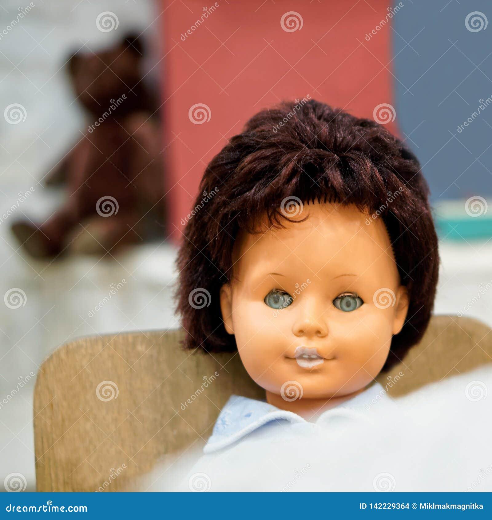 Старая игрушка - винтажная кукла с голубыми глазами сидит перед таблицей в высоком стульчике поле глубины отмелое