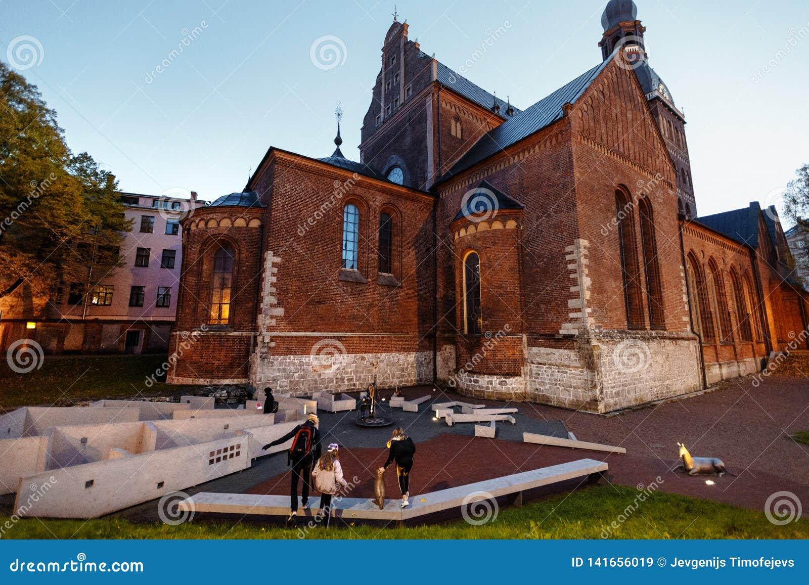 Старая Рига вечером, Латвия, Европа - люди идя в исторические улицы европейской столицы - laukums Doma с