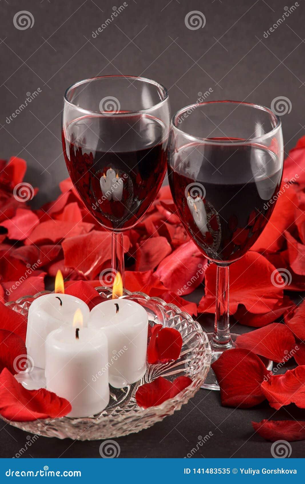 2 стекла вина, свечей и красных роз на черной предпосылке