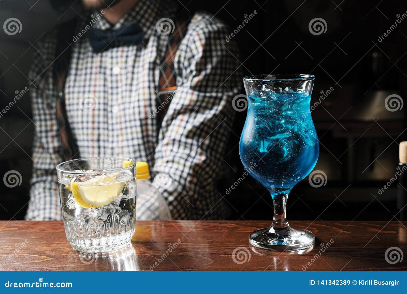 Стекла водки коктейлей голубой на предпосылке бара