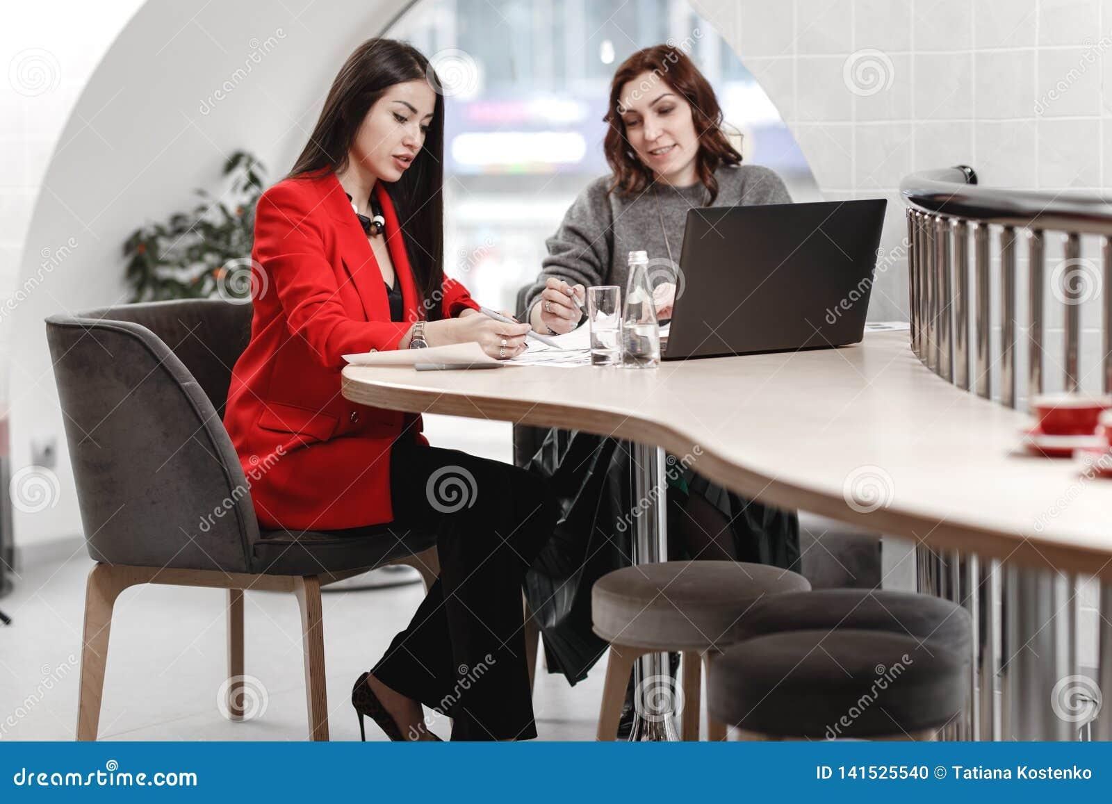 2 стильных дизайнера по интерьеру девушек работая в офисе на дизайн-проекте