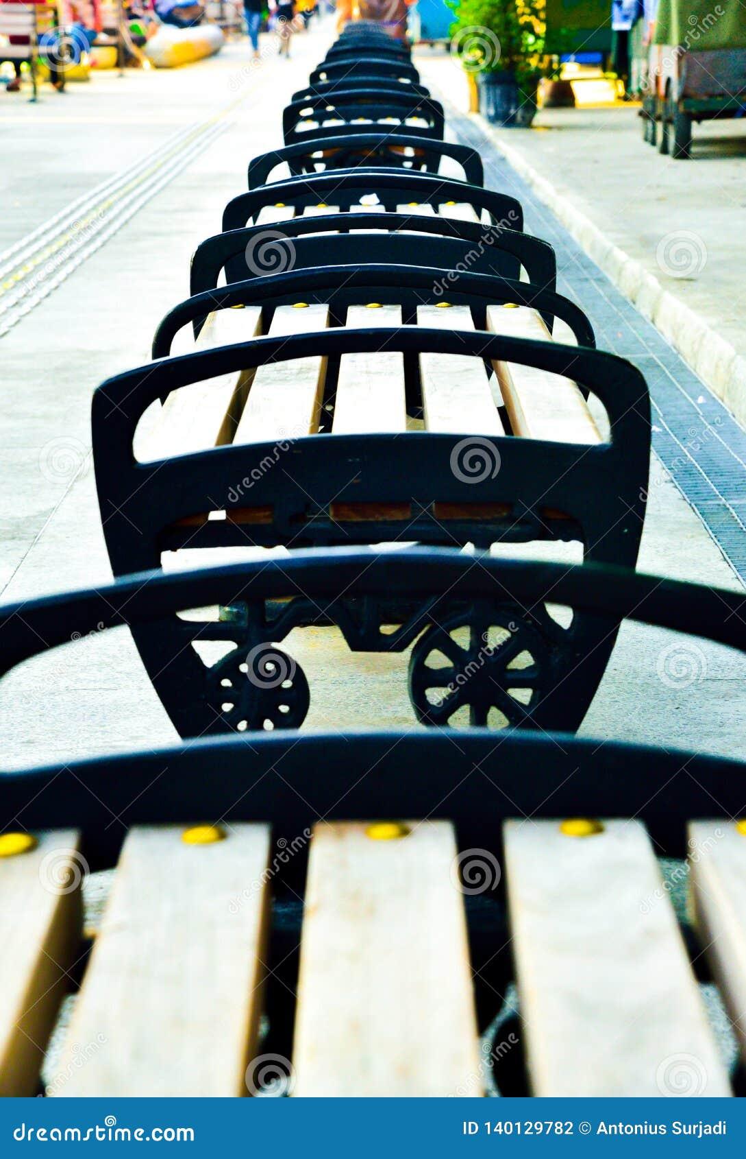 Строки стула древесины и металла на под открытым небом торговой улице в Юго-Восточной Азии