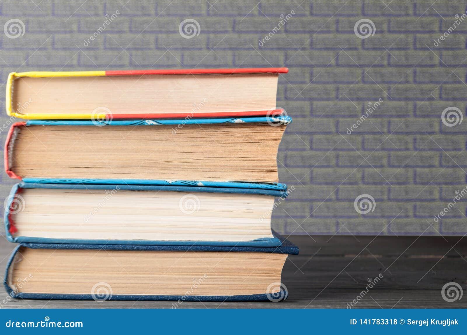 Стог книг с серой кирпичной кладкой на заднем плане, концепция образования, науки