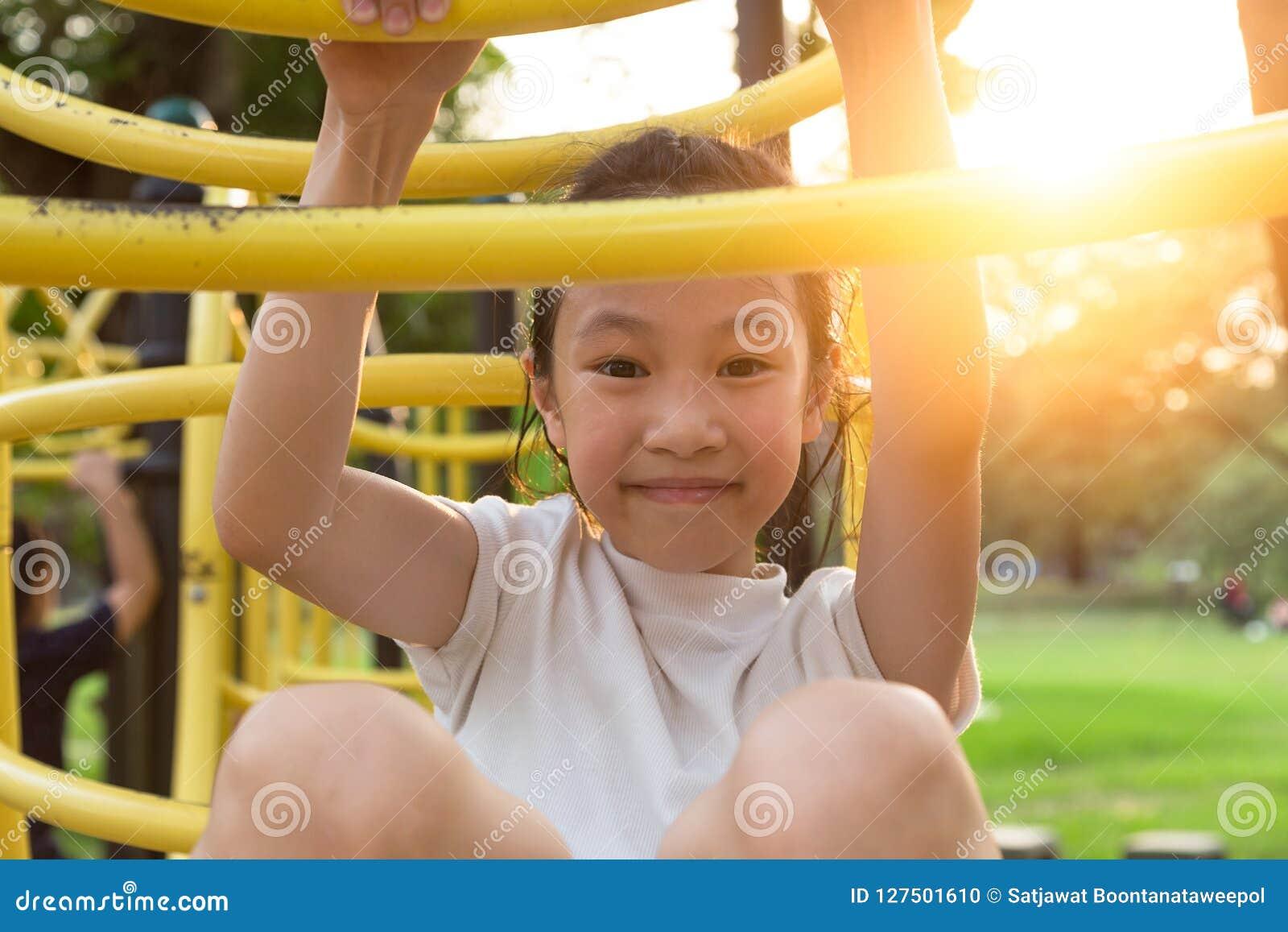 Счастливая, азиатская маленькая девочка играя на спортивной площадке на открытом воздухе и смотря камеру в парке, лето, концепцию