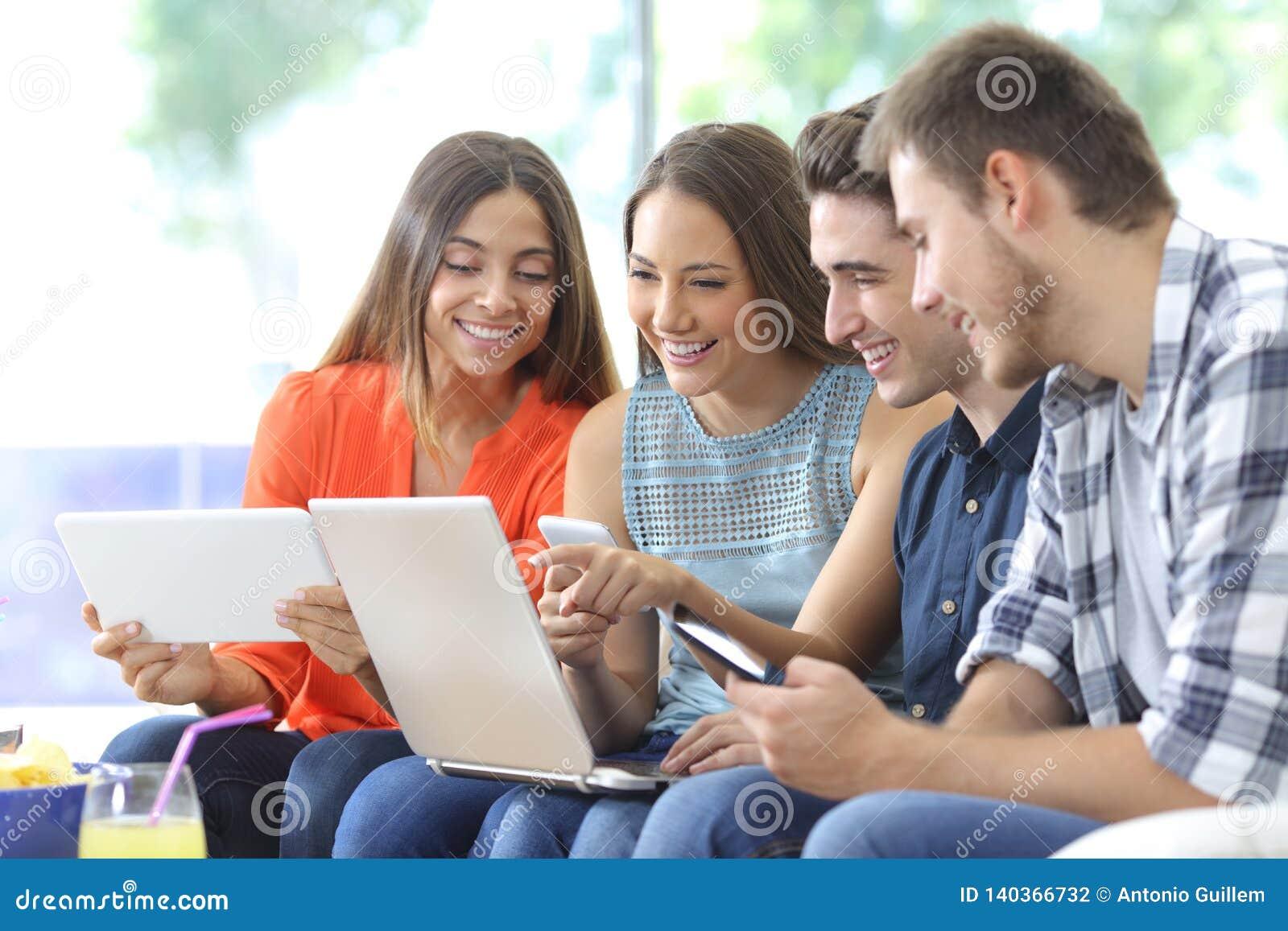 Счастливая группа в составе друзья проверяя множественные приборы