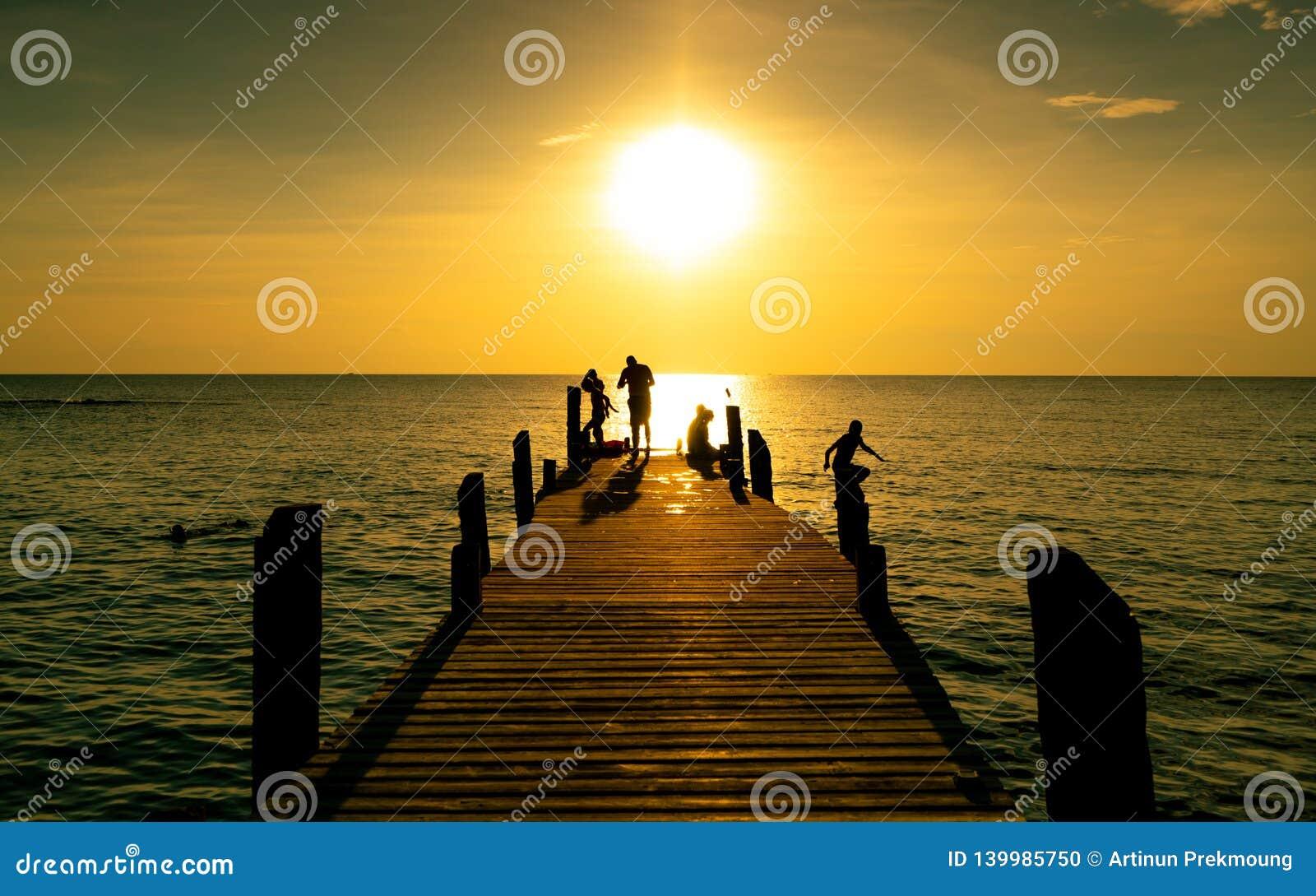 Счастливая игра семьи совместно на летних каникулах на деревянном мосте на заходе солнца Родитель и дети играя на пляже на праздн