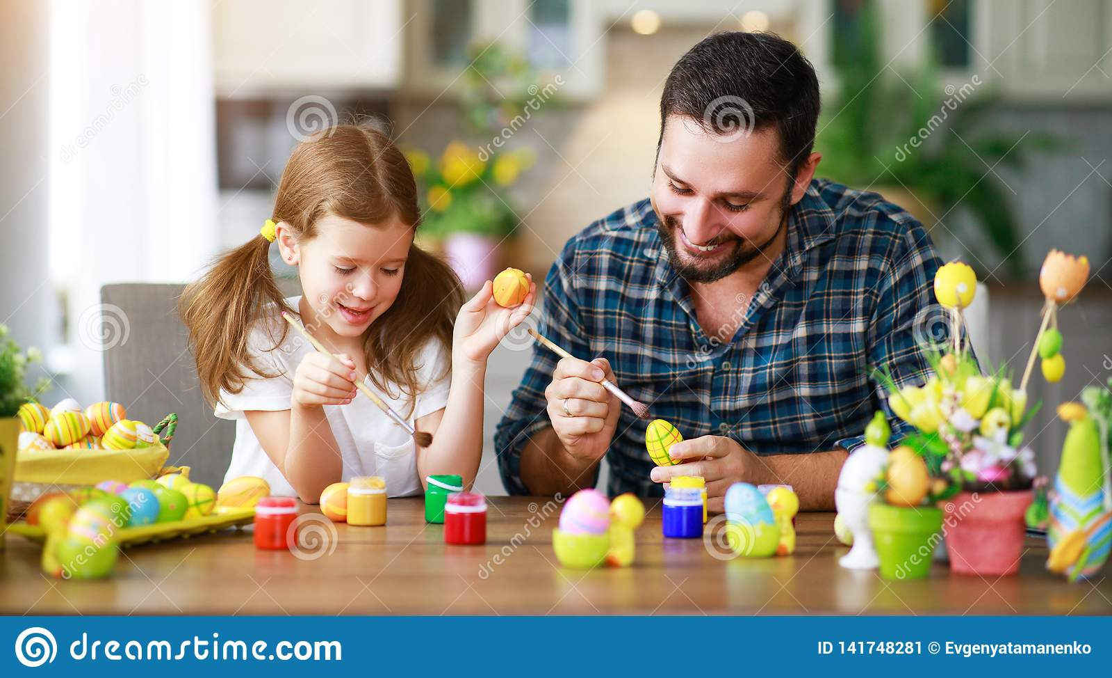 Счастливая пасха! отец и ребенок семьи с зайцами ушей получая готова на праздник
