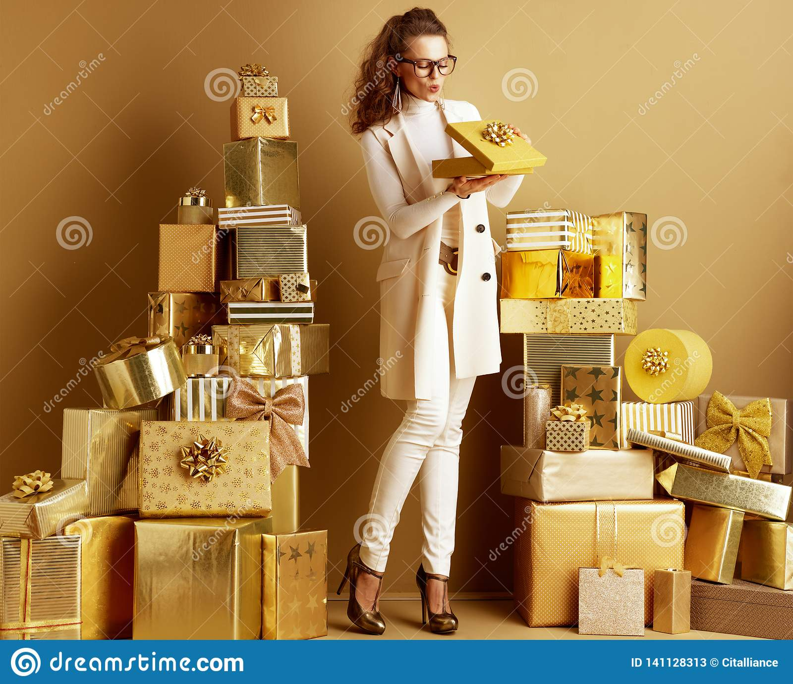 Счастливая элегантная женщина покупателя раскрывая золотую присутствующую коробку со смычком