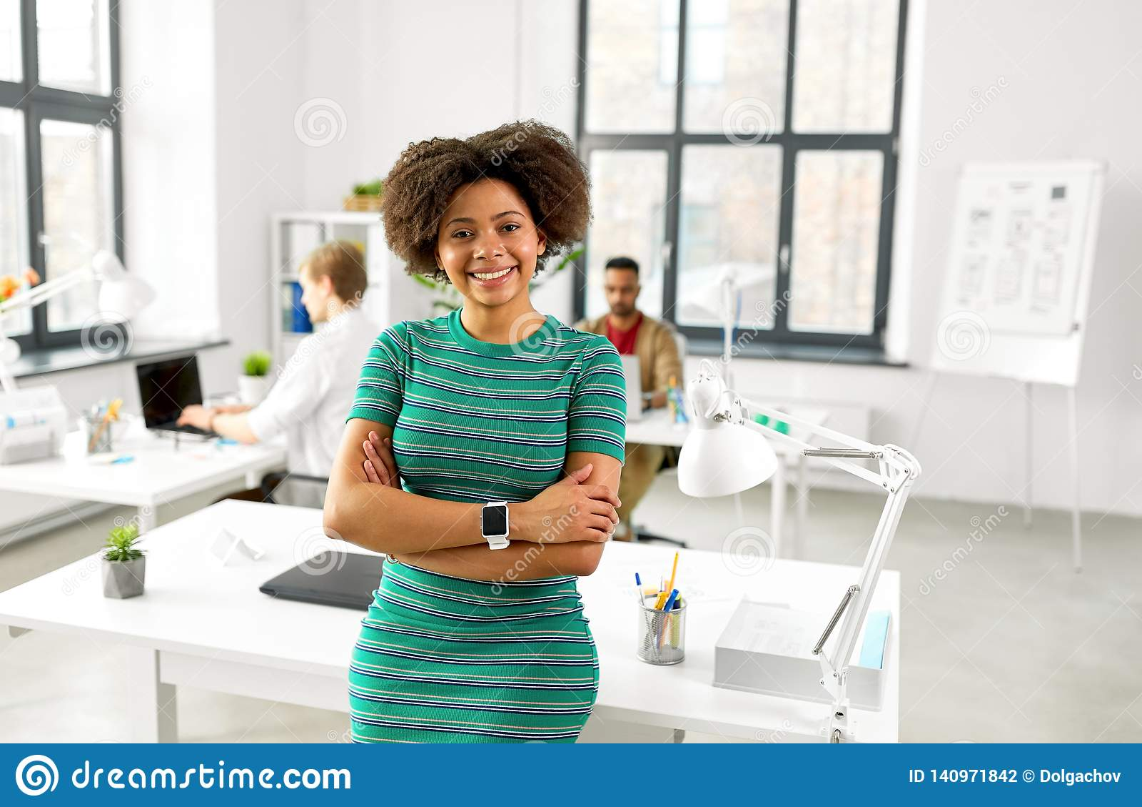 Счастливая усмехаясь Афро-американская женщина на офисе