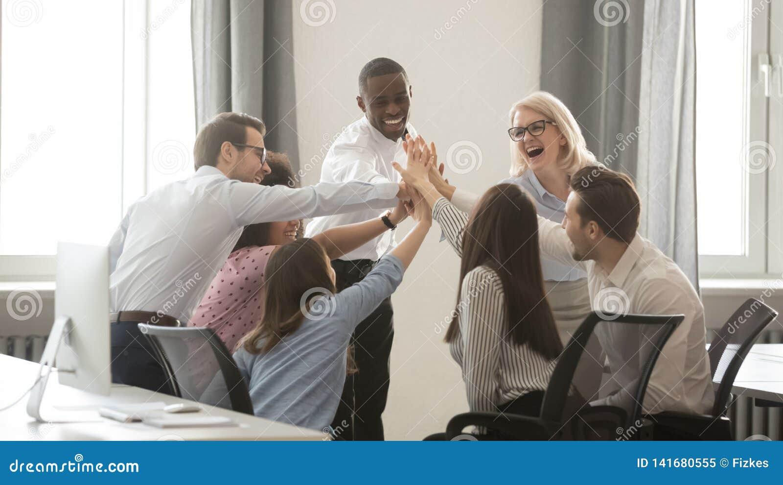 Счастливая разнообразная команда дела работников принималась за teambuilding давать высоко--5