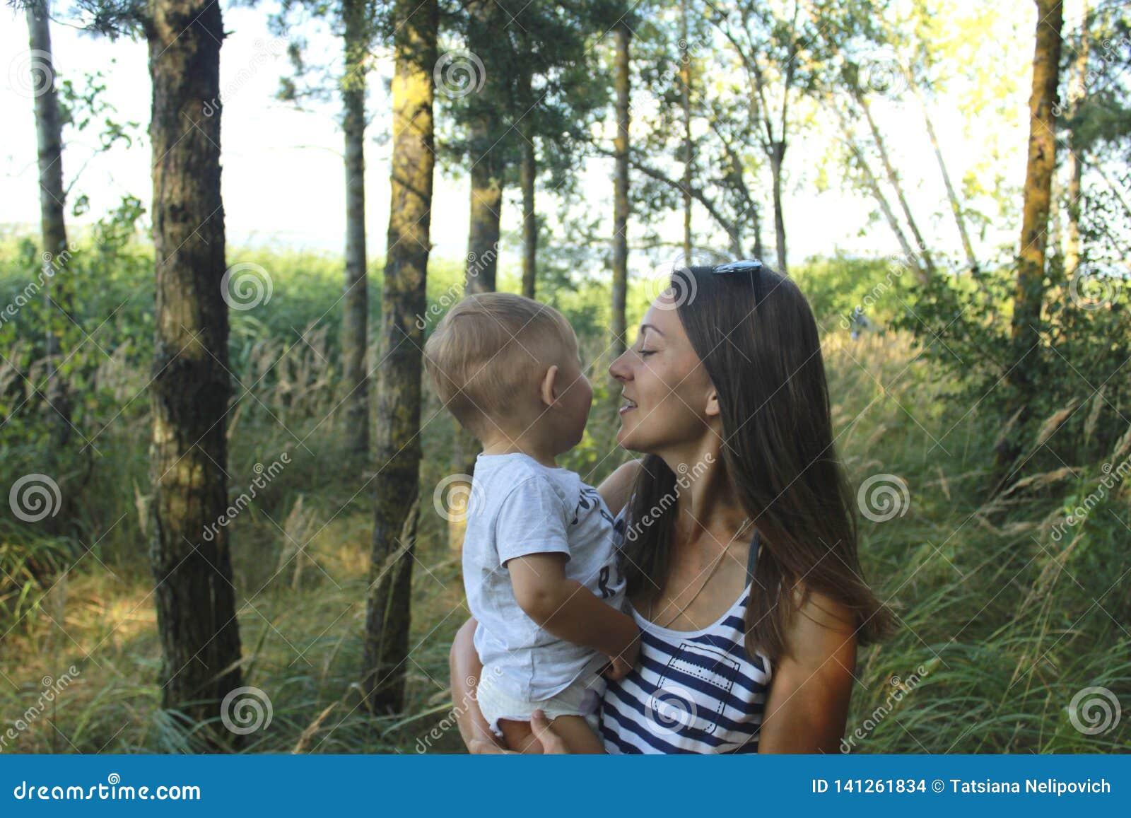 Счастливые мама и сын в маме соснового леса и сын Дня матери усмехаются и обнимаются Праздники семьи и общаться