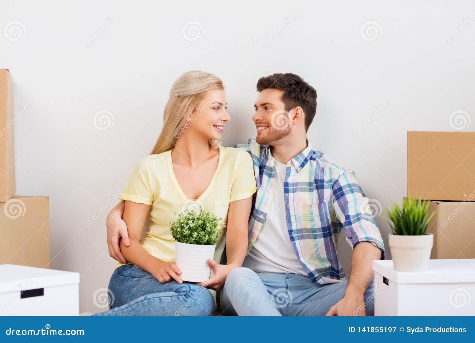 Счастливые пары при коробки двигая к новому дому