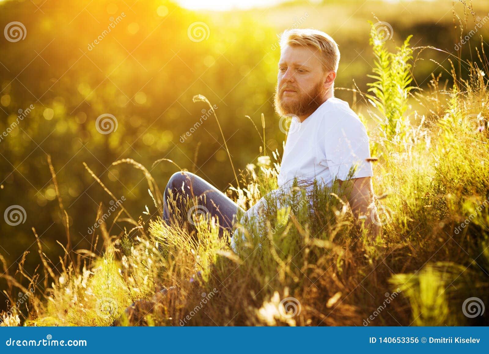 Счастливый бородатый парень отдыхая среди wildflowers
