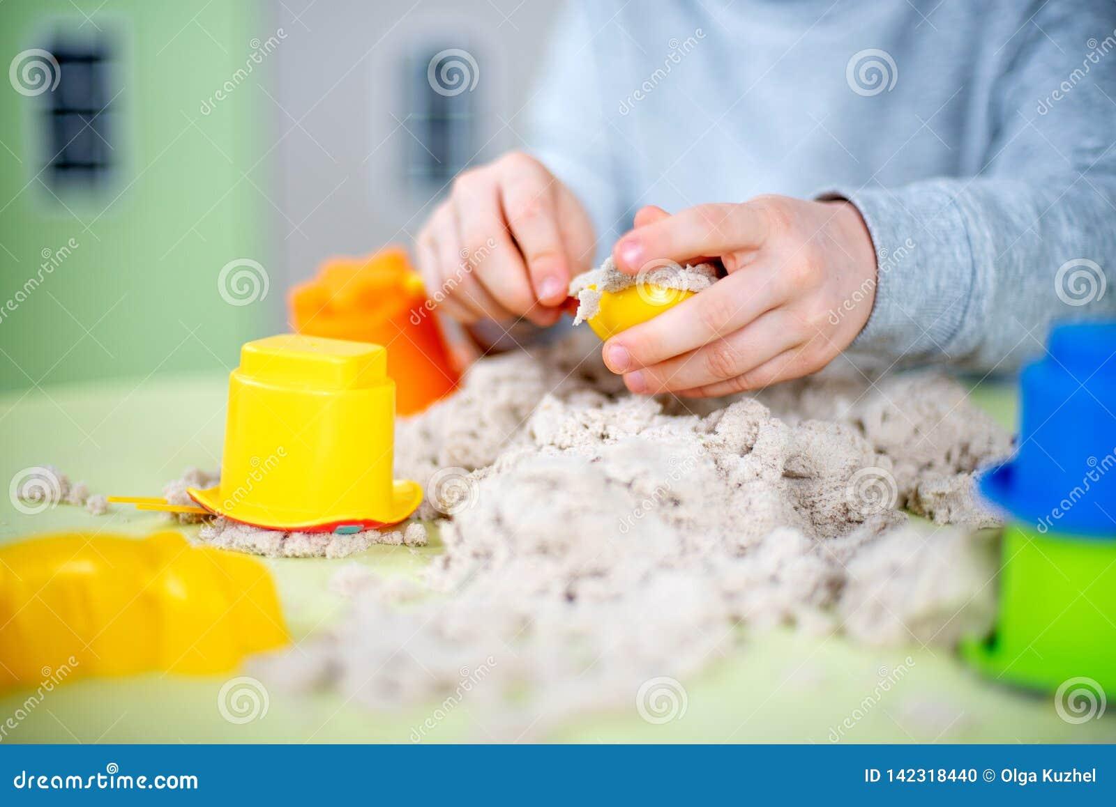 Счастливый мальчик играет кинетический песок дома