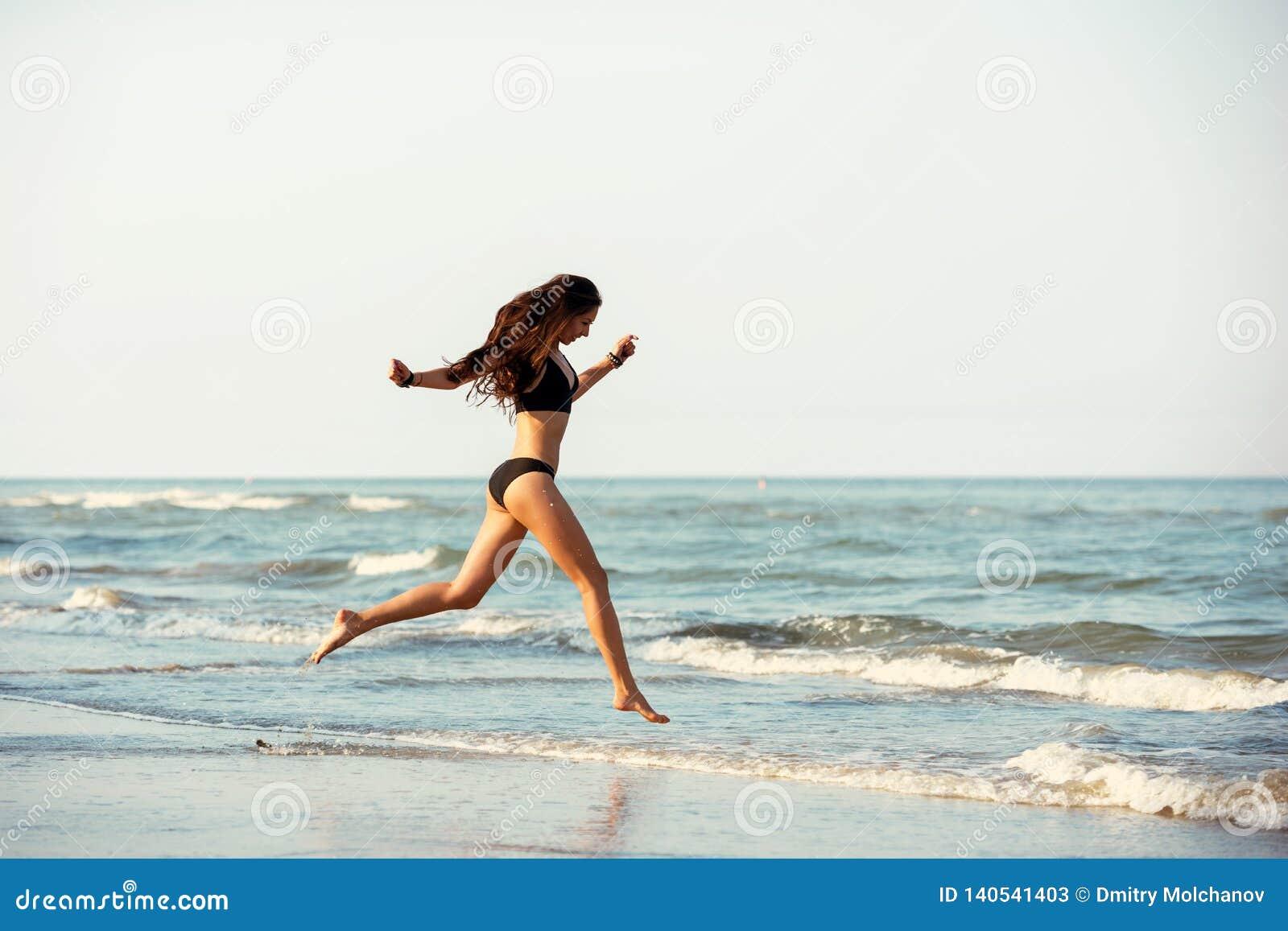 Счастливый тонкий пляж бега дамы на море