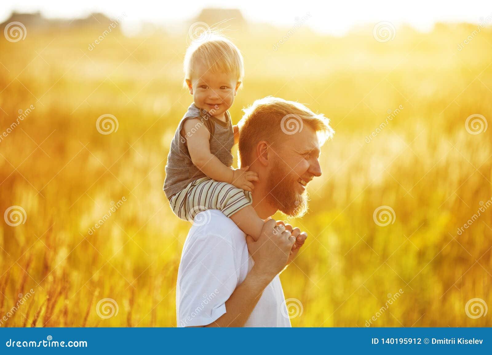 Счастливый отец с его меньшим сыном на его плечах