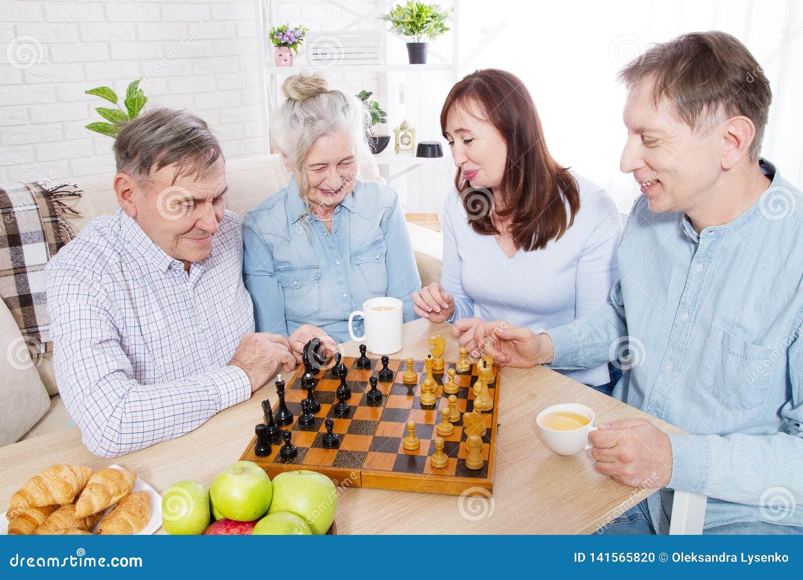 Счастливое время шахматов семьи на доме престарелых для пожилых людей Родители с детьми имеют беседу и отдых потехи Старшие пары