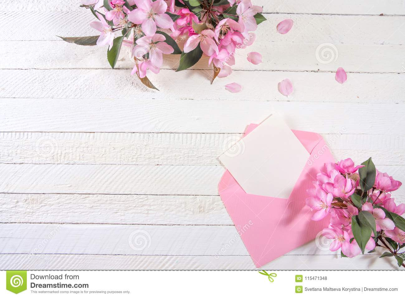 Сard with an pink envelope and pink flowers of apple tree on wooden board.