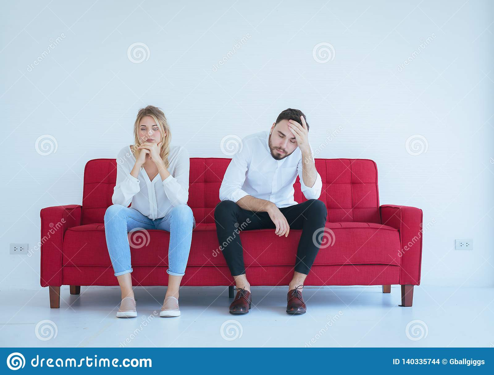 Ссора супруга с конфликтом жены и буря парами на красной софе, отрицательными эмоциями, копирует космос для текста, белой предпос
