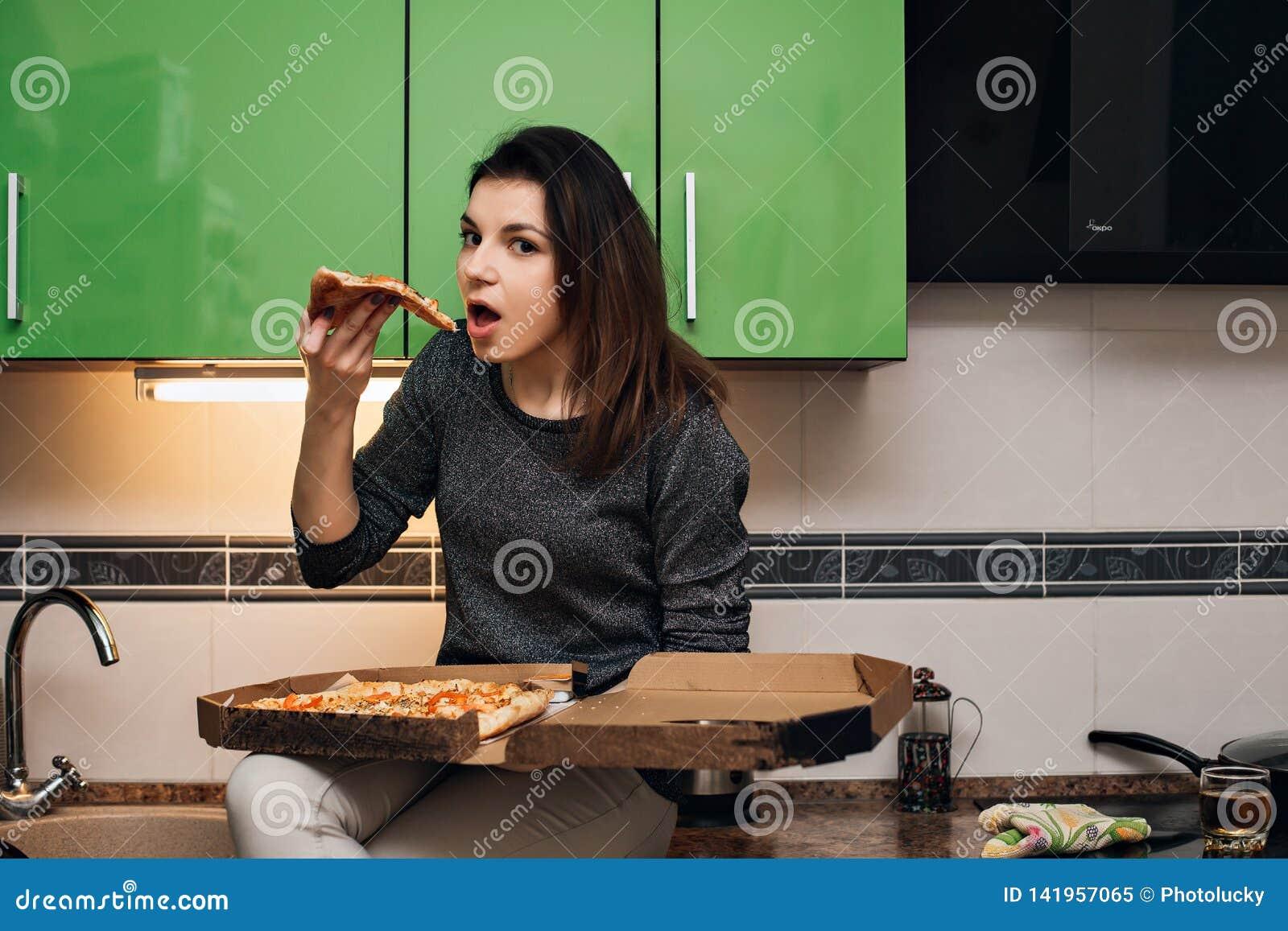 Эмоциональная девушка есть и держа горячую итальянскую пиццу
