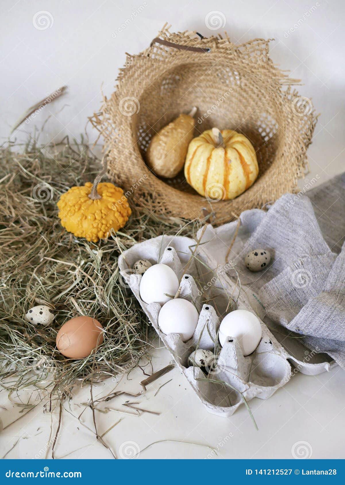 Яйца и яйца триперсток в пакете, тыквы, сено, концепция пасхи, подготовка на праздник, сбор, сезонные праздники
