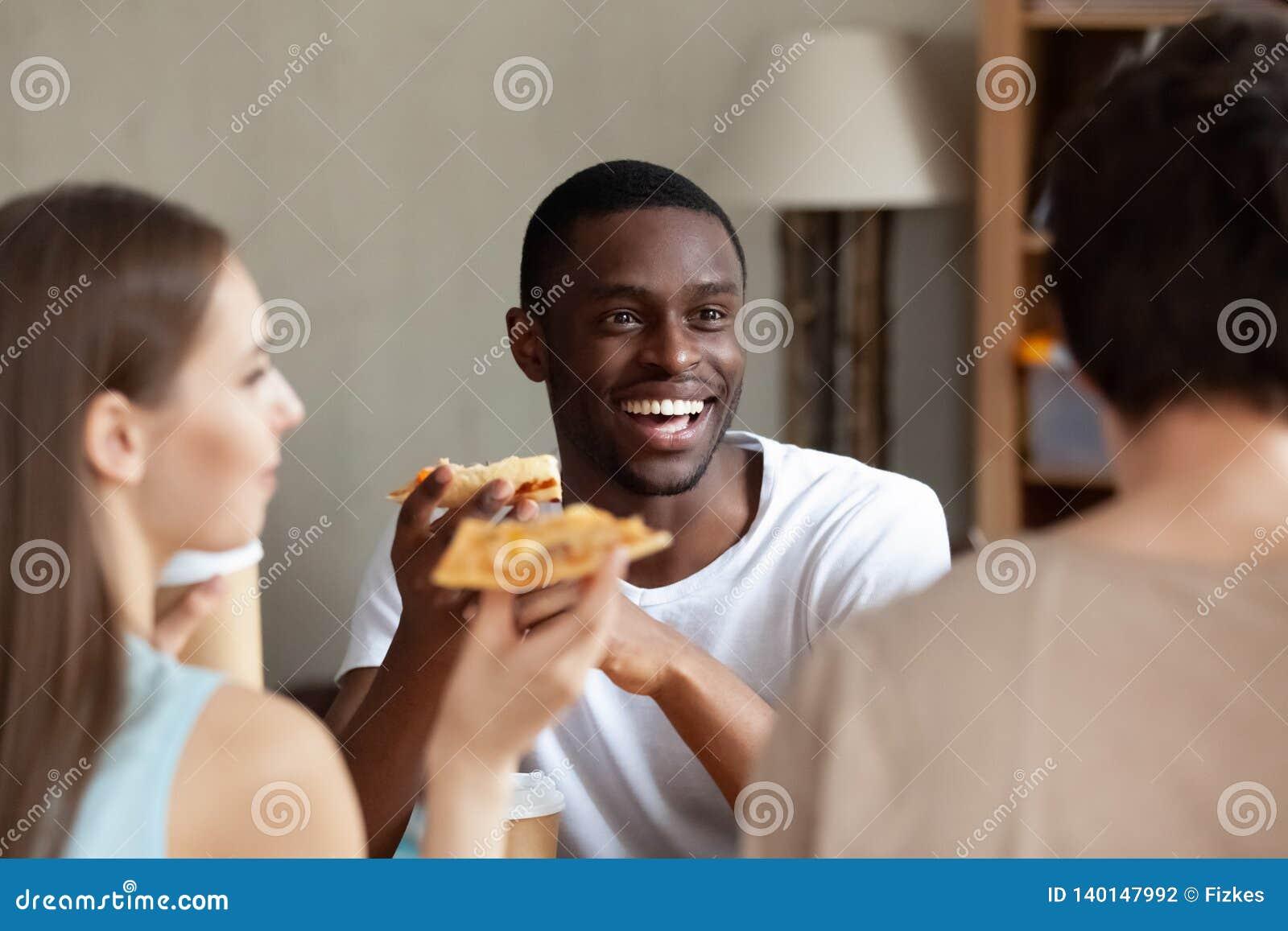 Усмехаясь Афро-американский человек есть пиццу, беседуя с друзьями