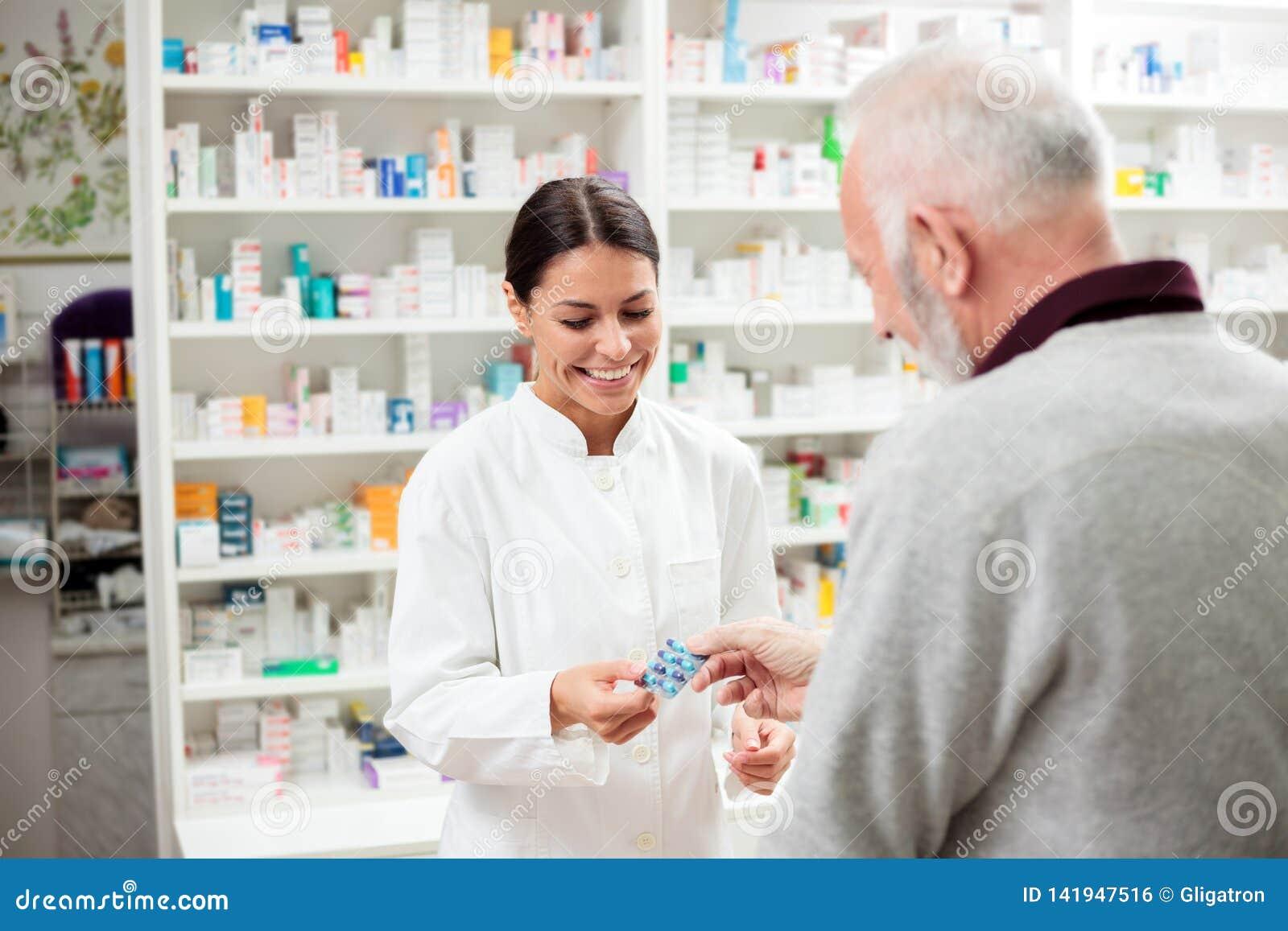 Усмехаясь молодой женский аптекарь давая таблетки лекарства рецепта старшему мужскому пациенту