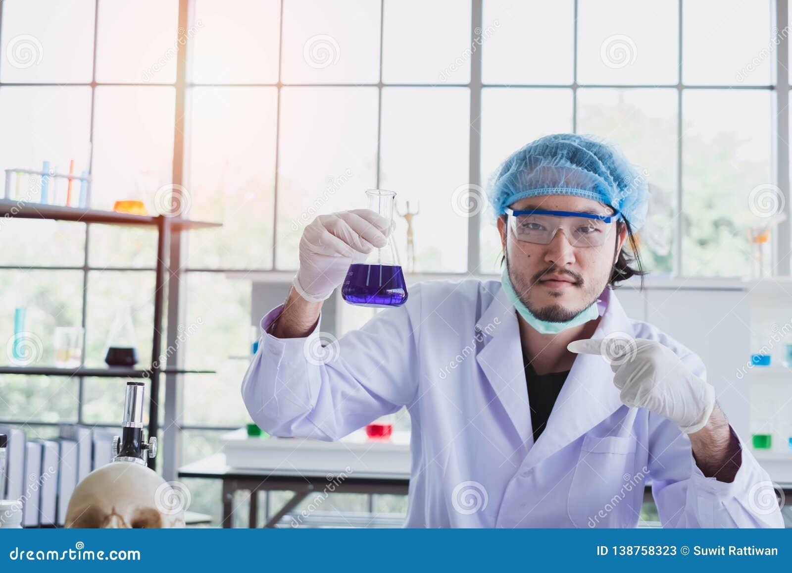 Успешный мужской химик рассматривает его новое нововведение в лаборатории