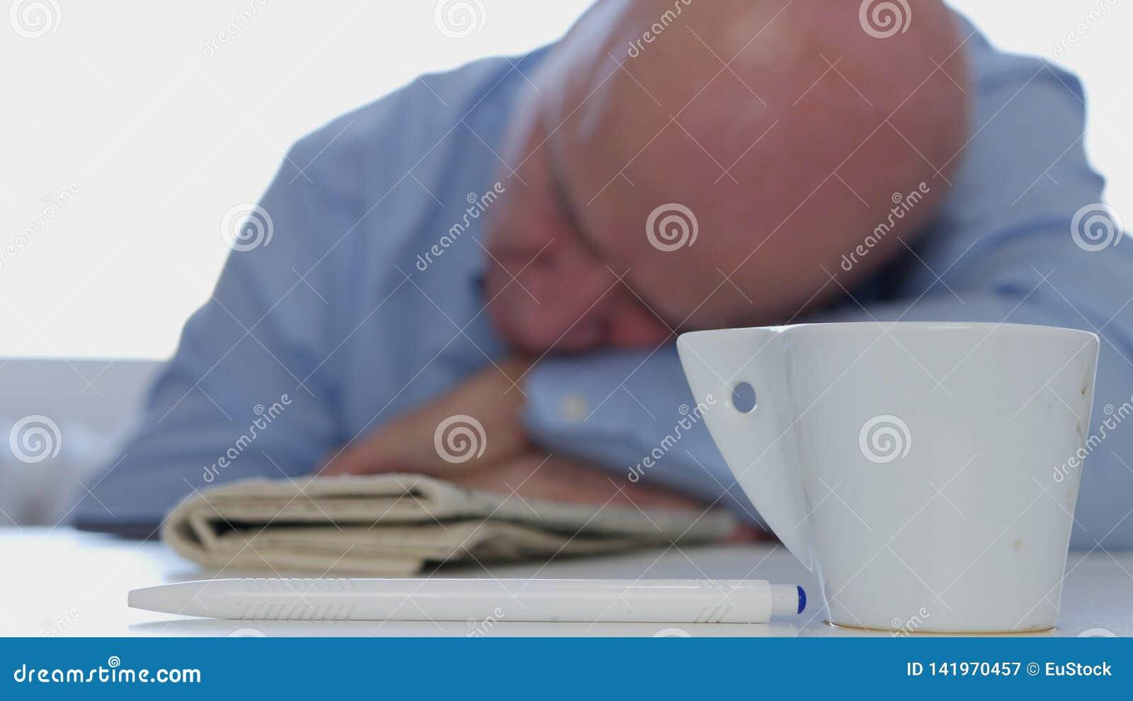 Уставший бизнесмен Napping дома с кофе и газетой на таблице