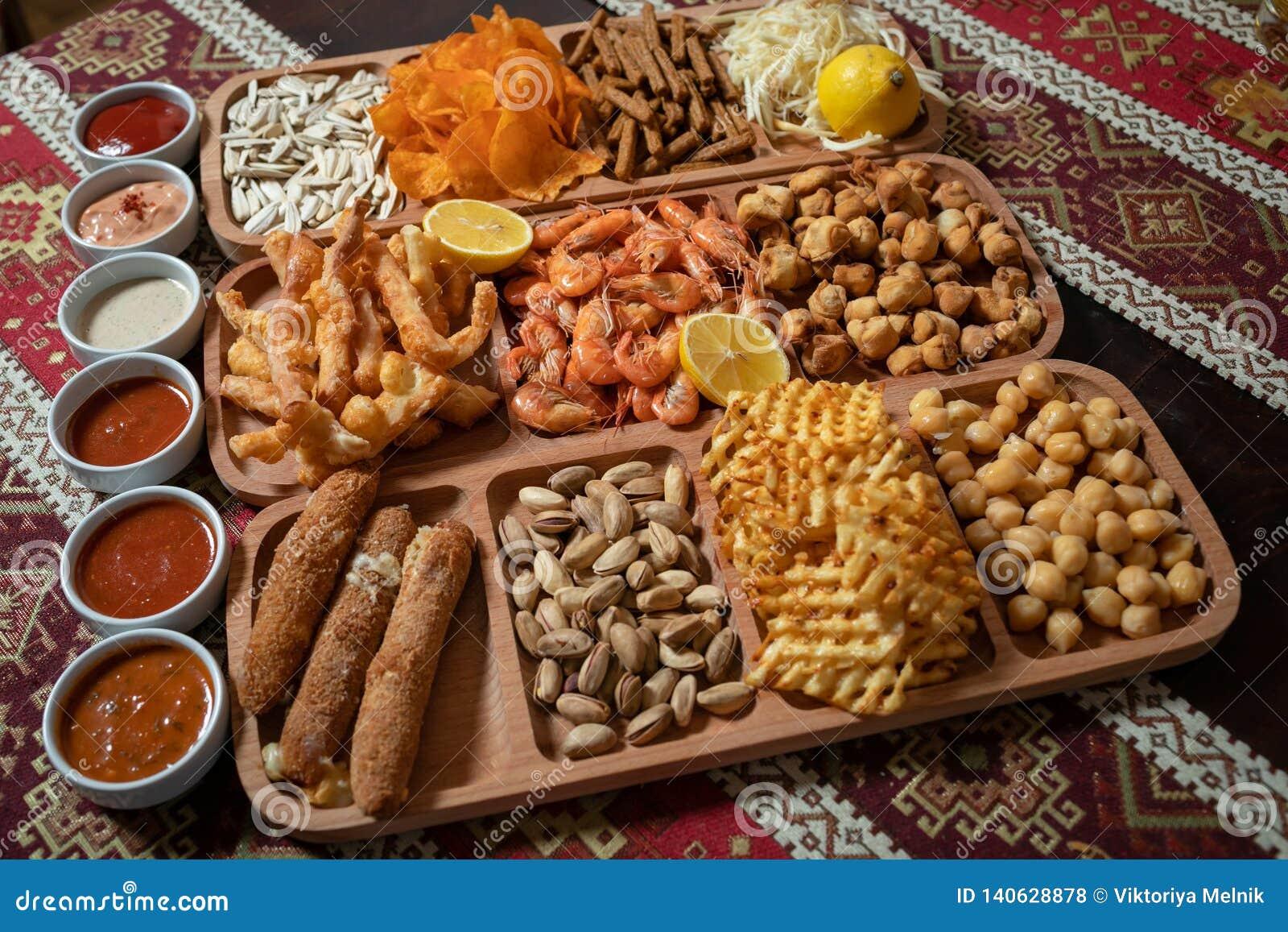 Установите закусок пива, 11 разнообразий и 6 соусов на деревянном столе со скатертью с национальными картинами