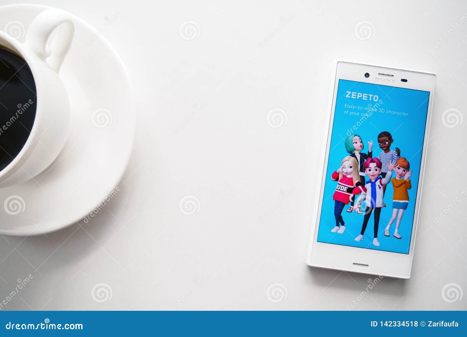 Уфа, Россия - 15-ое марта 2019: Применение ZEPETO на экране смартфона андроида, телефоне и кофейной чашке на белой предпосылке, э