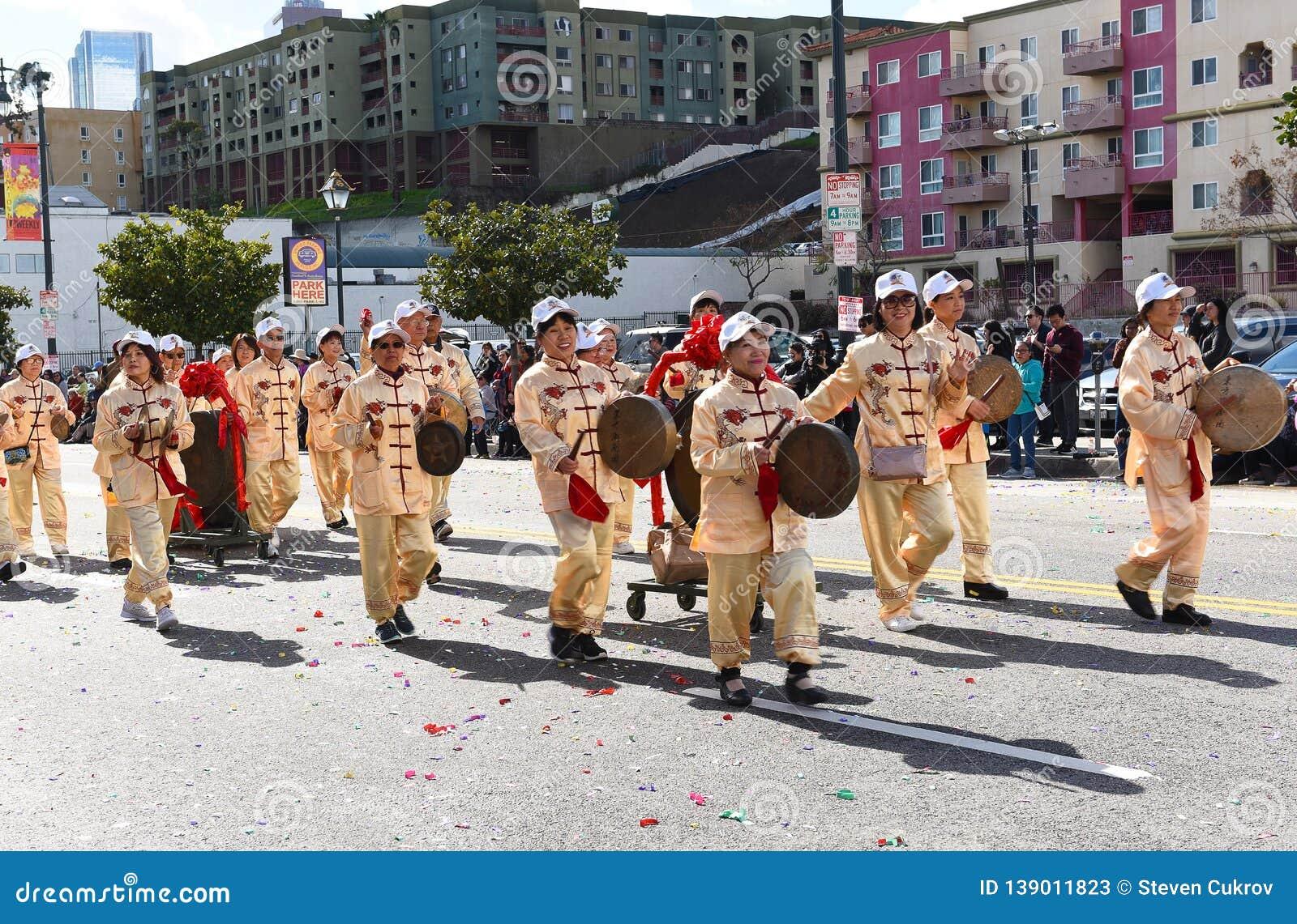 Участники марша играя китайские аппаратуры на параде Нового Года Лос-Анджелеса китайском