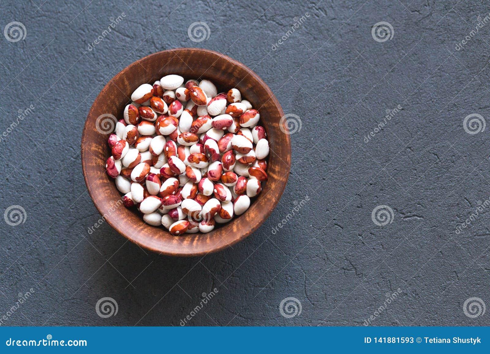 Шар различных фасолей haricot на каменной таблице, взгляде сверху