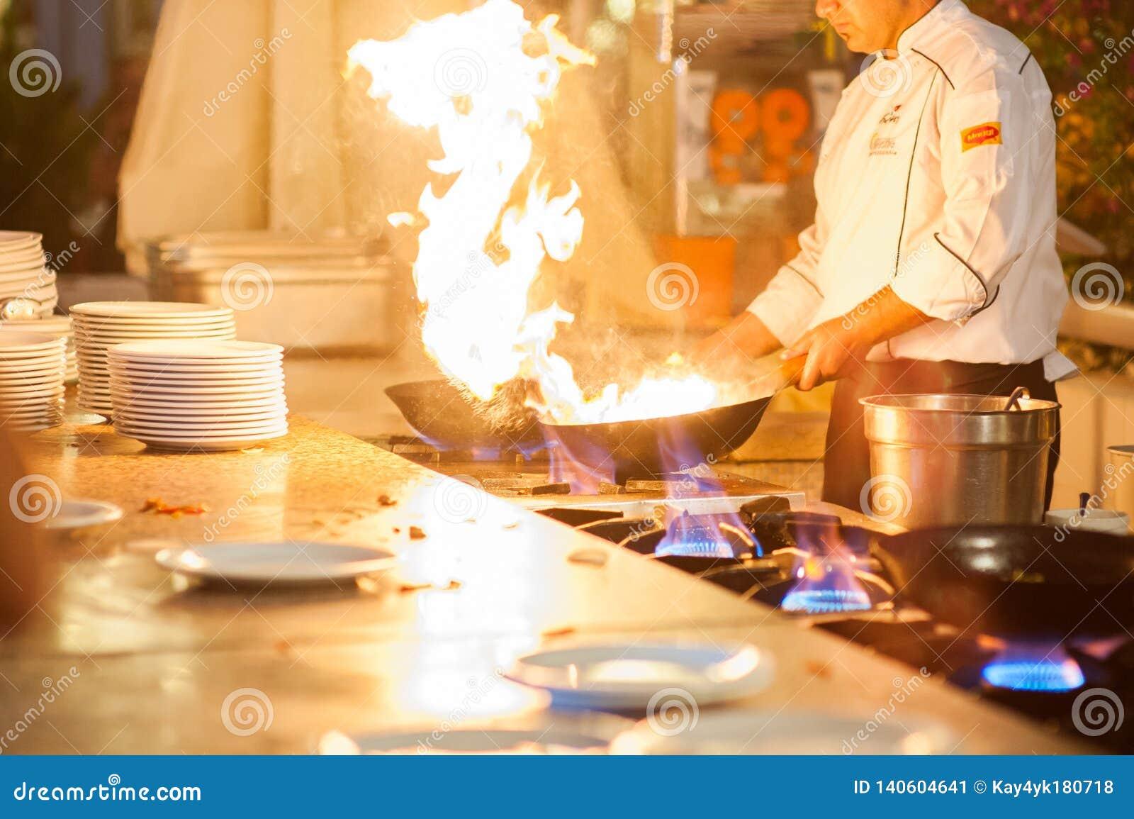 Шеф-повар в кухне ресторана на плите с лотком, повара над высокой жарой