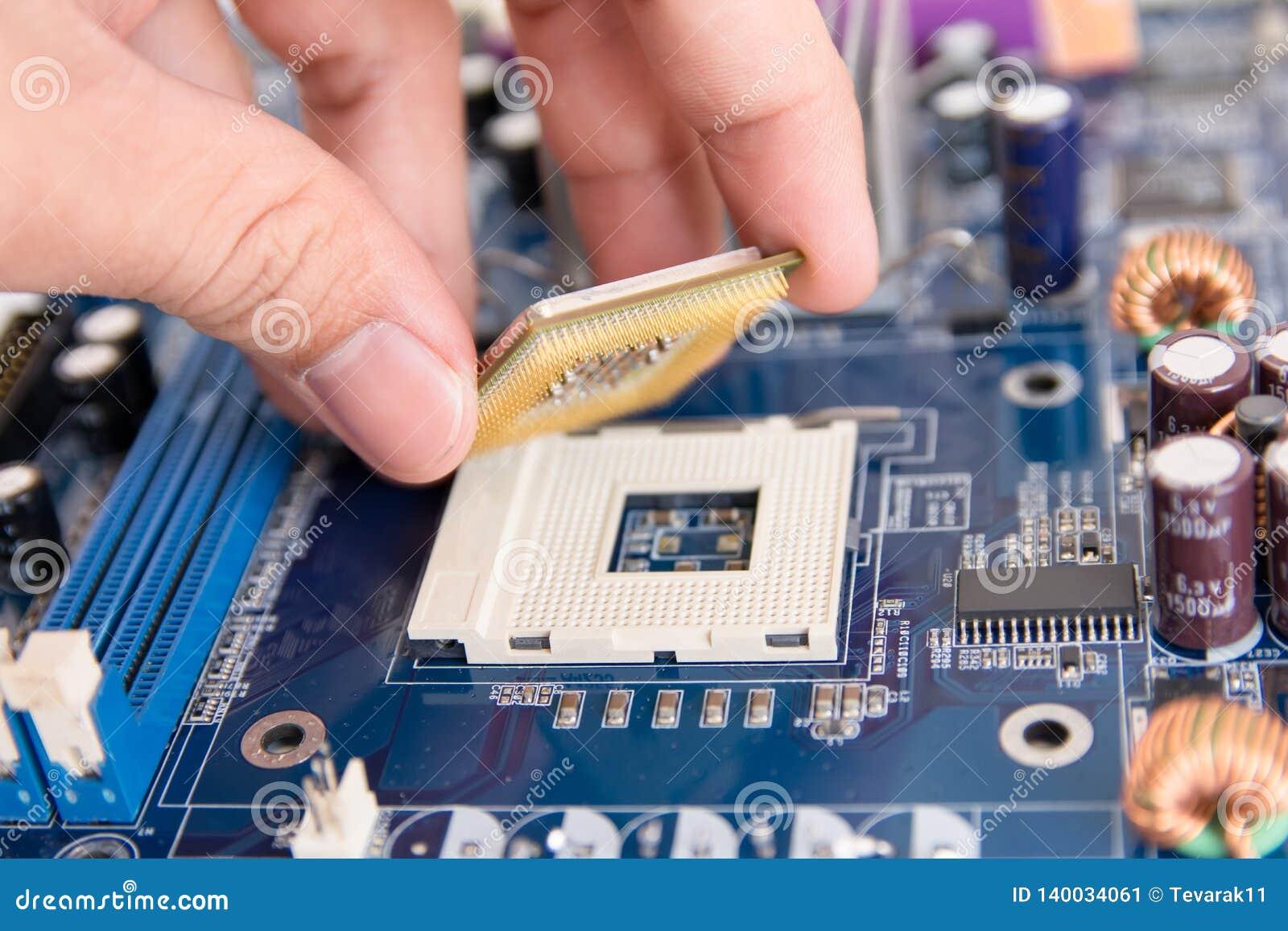 Техник устанавливая микропроцессор обломока C.P.U. к гнезду на материнскую плату