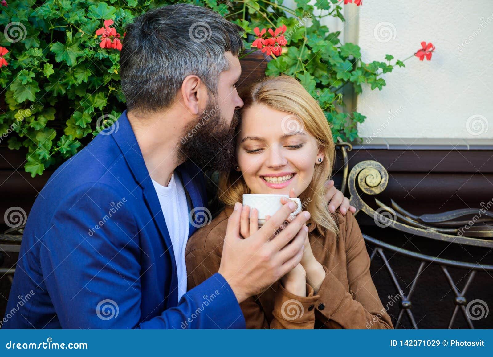 Терраса кафа пар прижимаясь Пары в влюбленности сидят терраса кафа наслаждаются кофе Приятные выходные семьи Исследуйте кафе и