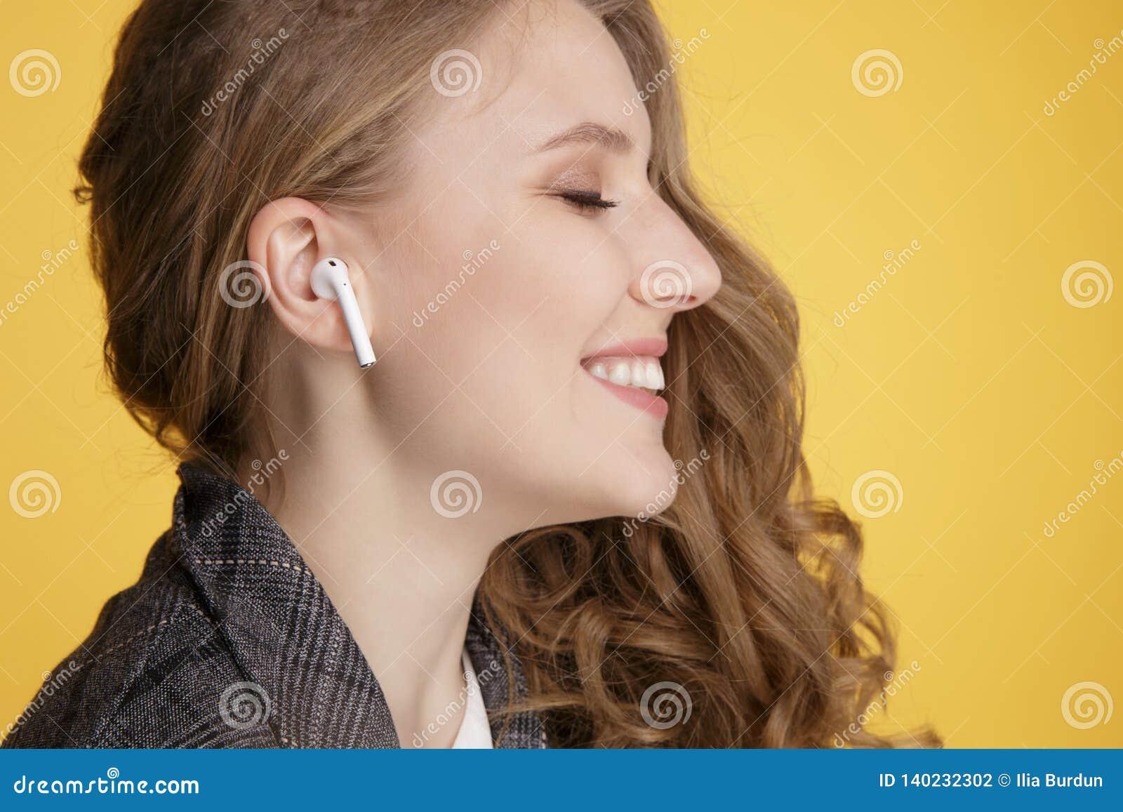 Тула, Россия - 24-ОЕ ЯНВАРЯ 2019: Радиотелеграф Яблока AirPods музыки счастливой женщины слушая