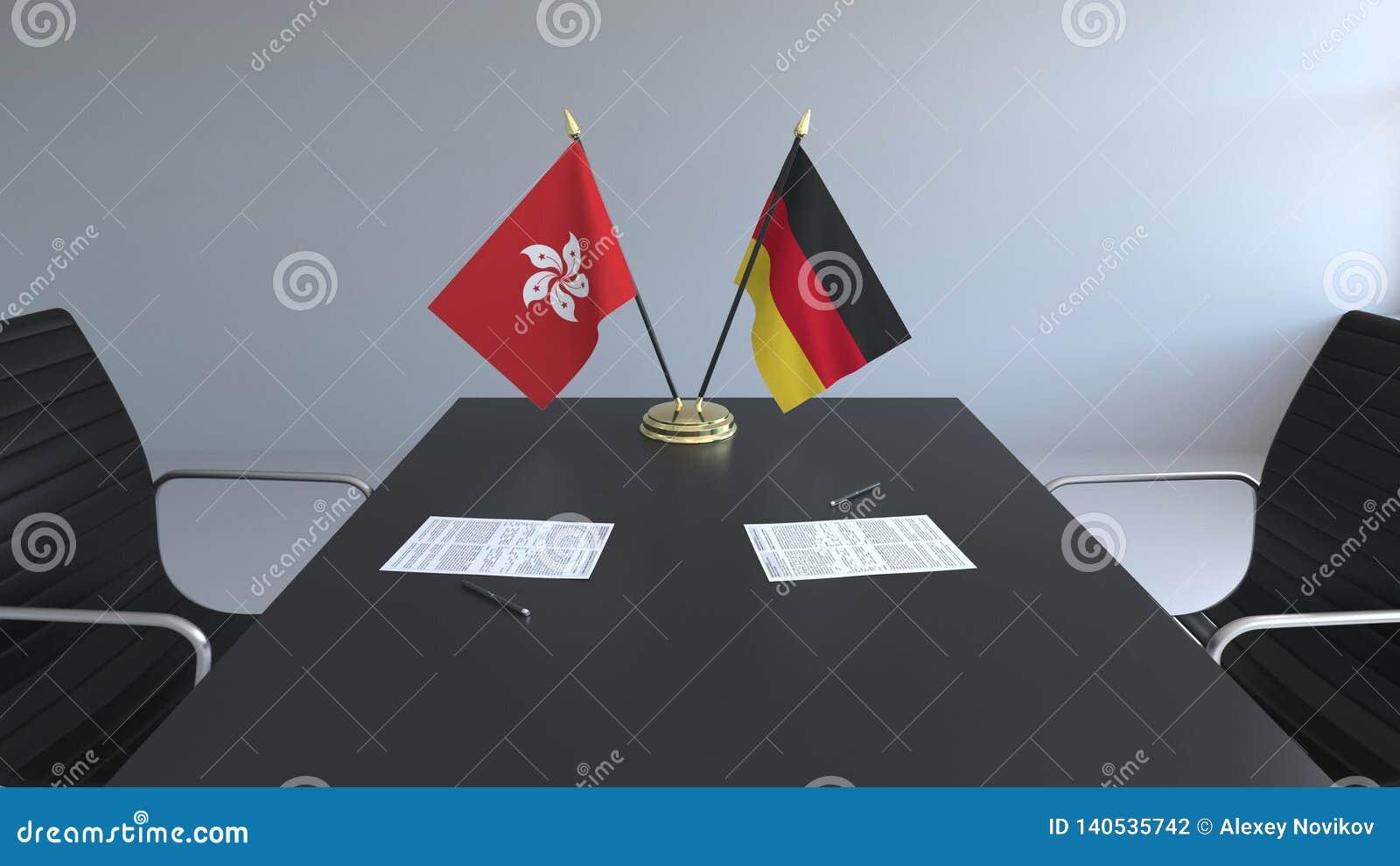 Флаги Гонконга и Германии и бумаги на таблице Переговоры и подписание международного соглашения схематическо
