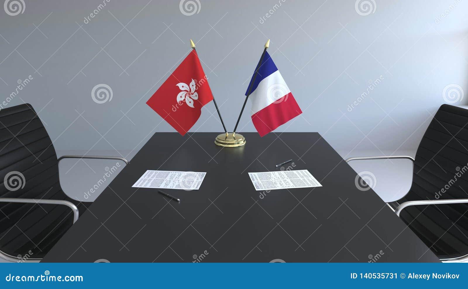 Флаги Гонконга и Франции и бумаги на таблице Переговоры и подписание международного соглашения схематическо