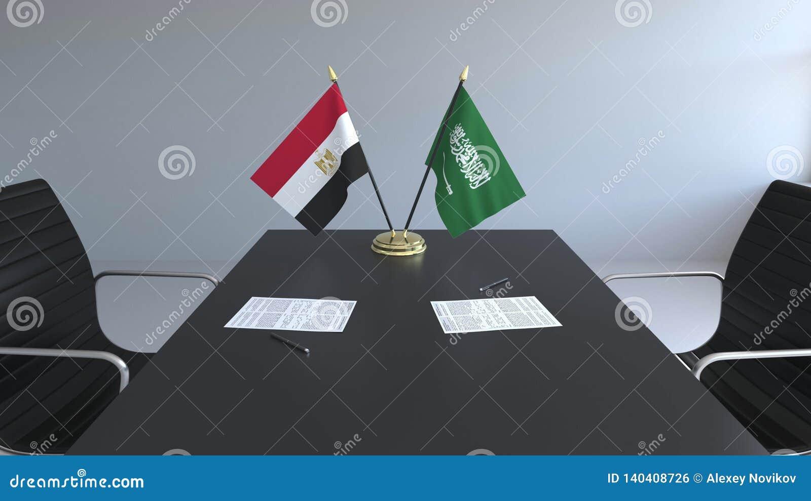 Флаги Египта и Саудовской Аравии и бумаги на таблице Переговоры и подписание международного соглашения схематическо