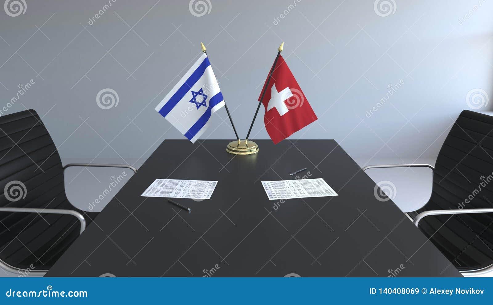 Флаги Израиля и Швейцарии и бумаги на таблице Переговоры и подписание международного соглашения схематическо