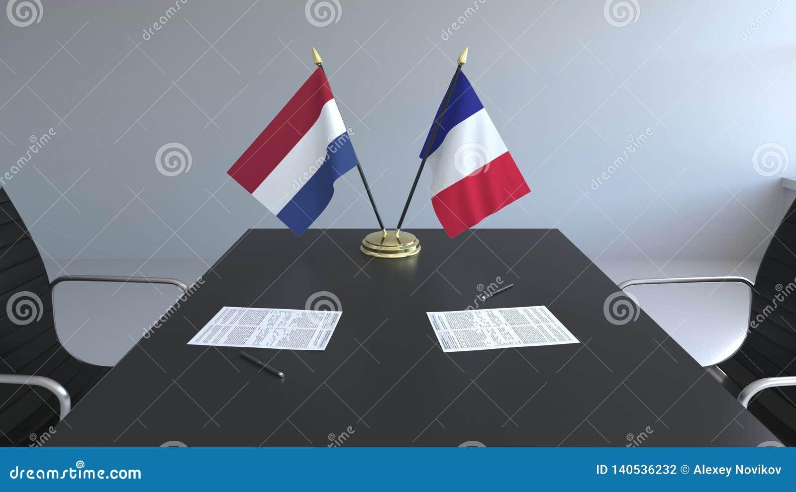 Флаги Нидерланд и Франции и бумаги на таблице Переговоры и подписание международного соглашения схематическо