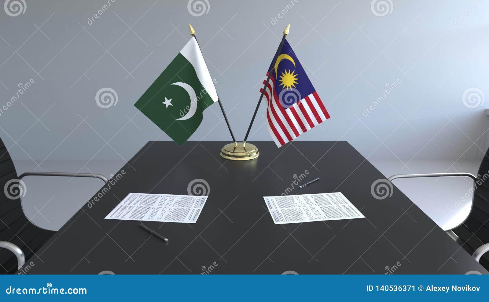 Флаги Пакистана и Малайзии и бумаги на таблице Переговоры и подписание международного соглашения схематическо