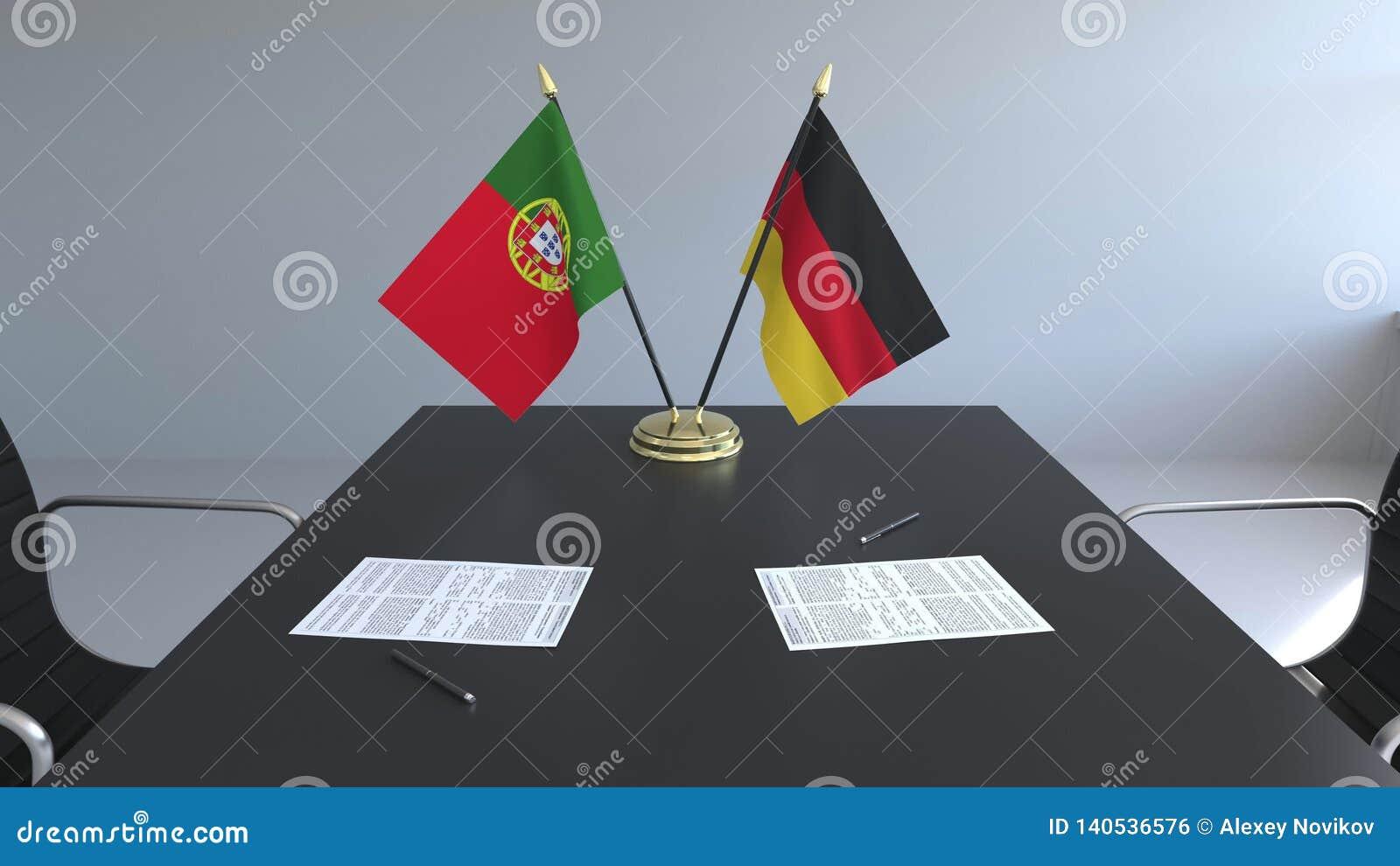 Флаги Португалии и Германии и бумаги на таблице Переговоры и подписание международного соглашения схематическо